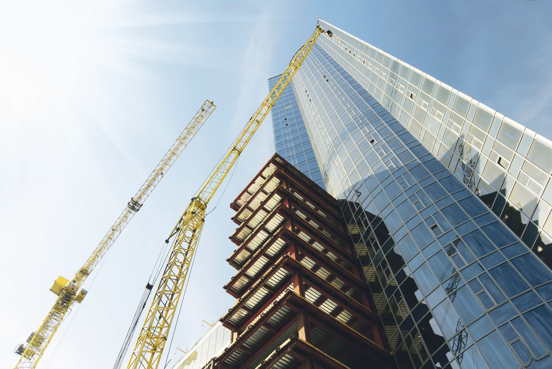Wolkenkratzer mit Baukränen (von unten fotografiert)
