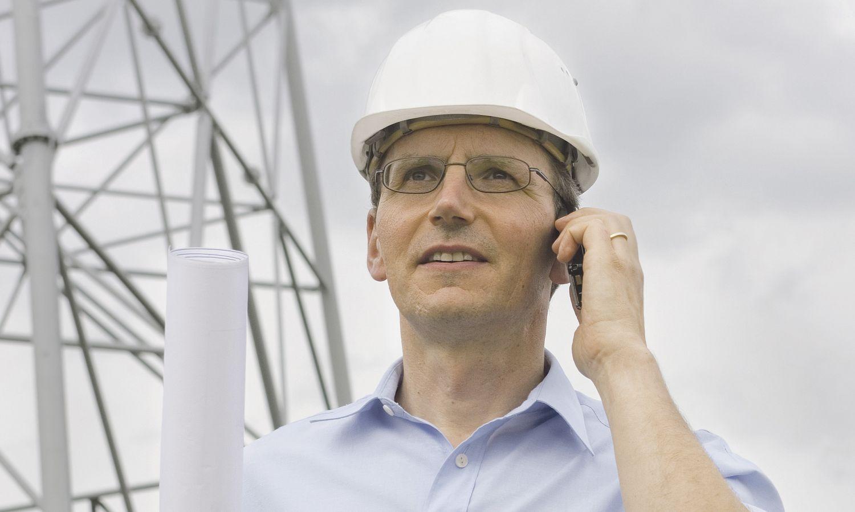 Bauherr telefoniert auf einer Baustelle